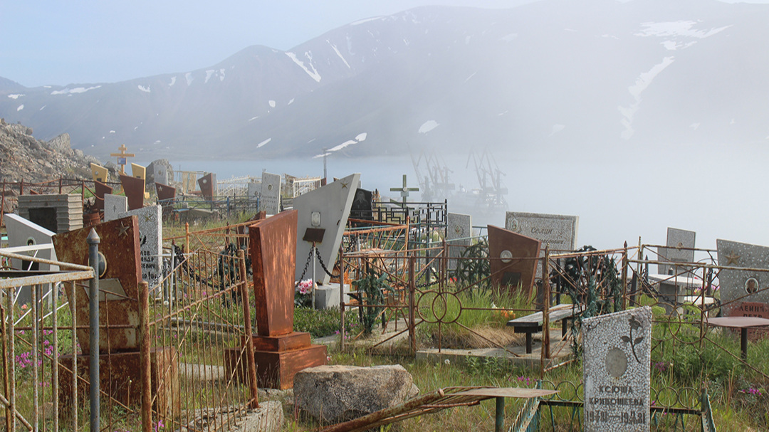 Provideniya cemetery, with our ship in the distant fog looking small against Soviet-era coal loaders.