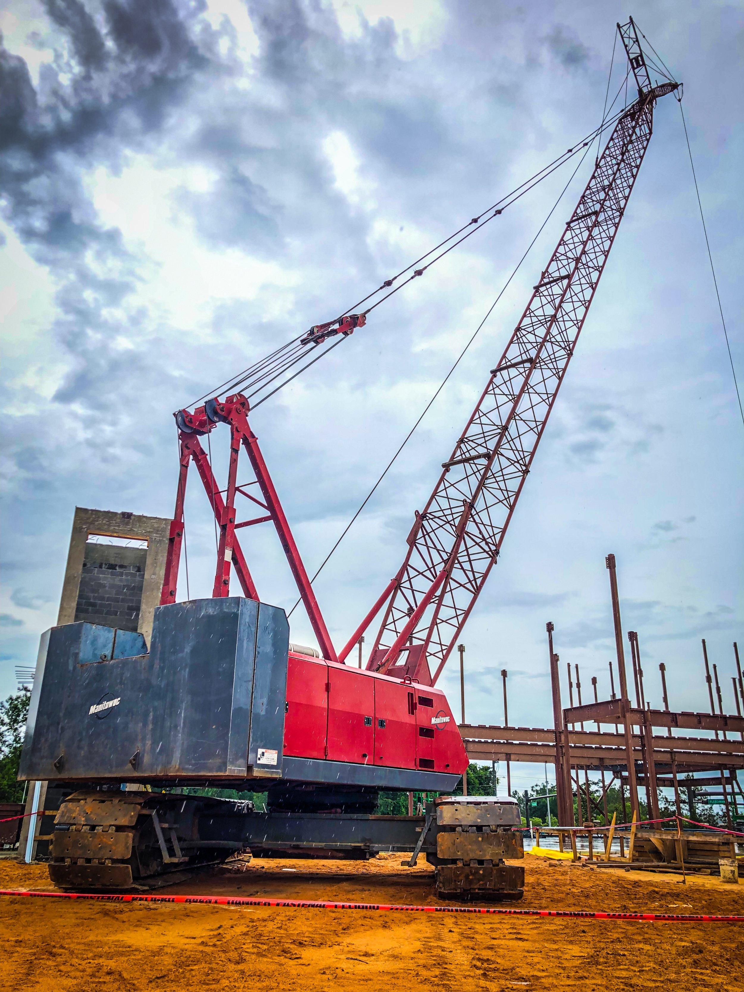 100 ton crawler crane on red beam hanging construction.JPEG