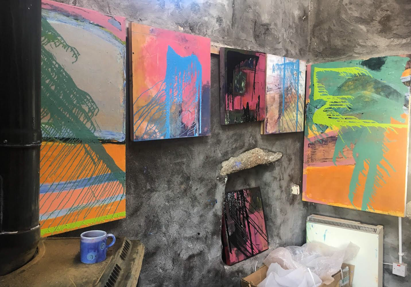 6 'poured paint' pieces on board and canvas on the drying wall of Liz's studio. All 6 are now at Mark Borghi Fine Art in Palm Beach, Florida.
