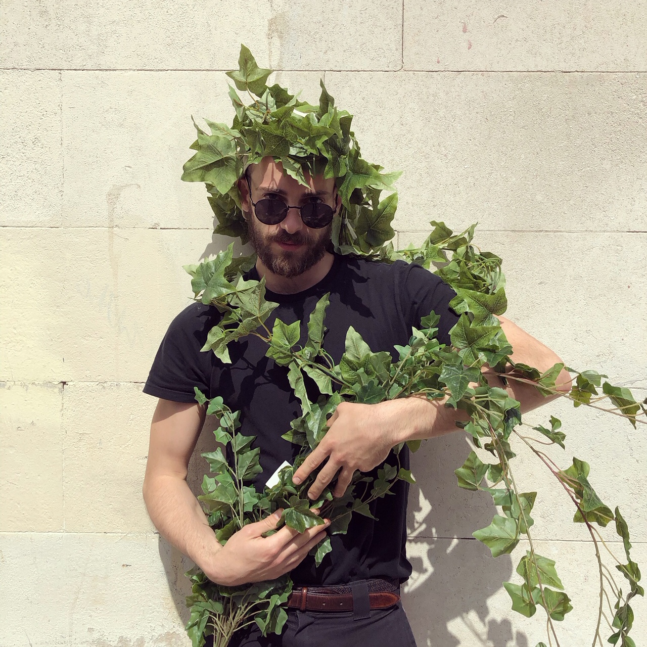Ali wearing artificial ivy being used in an artificial living wall.
