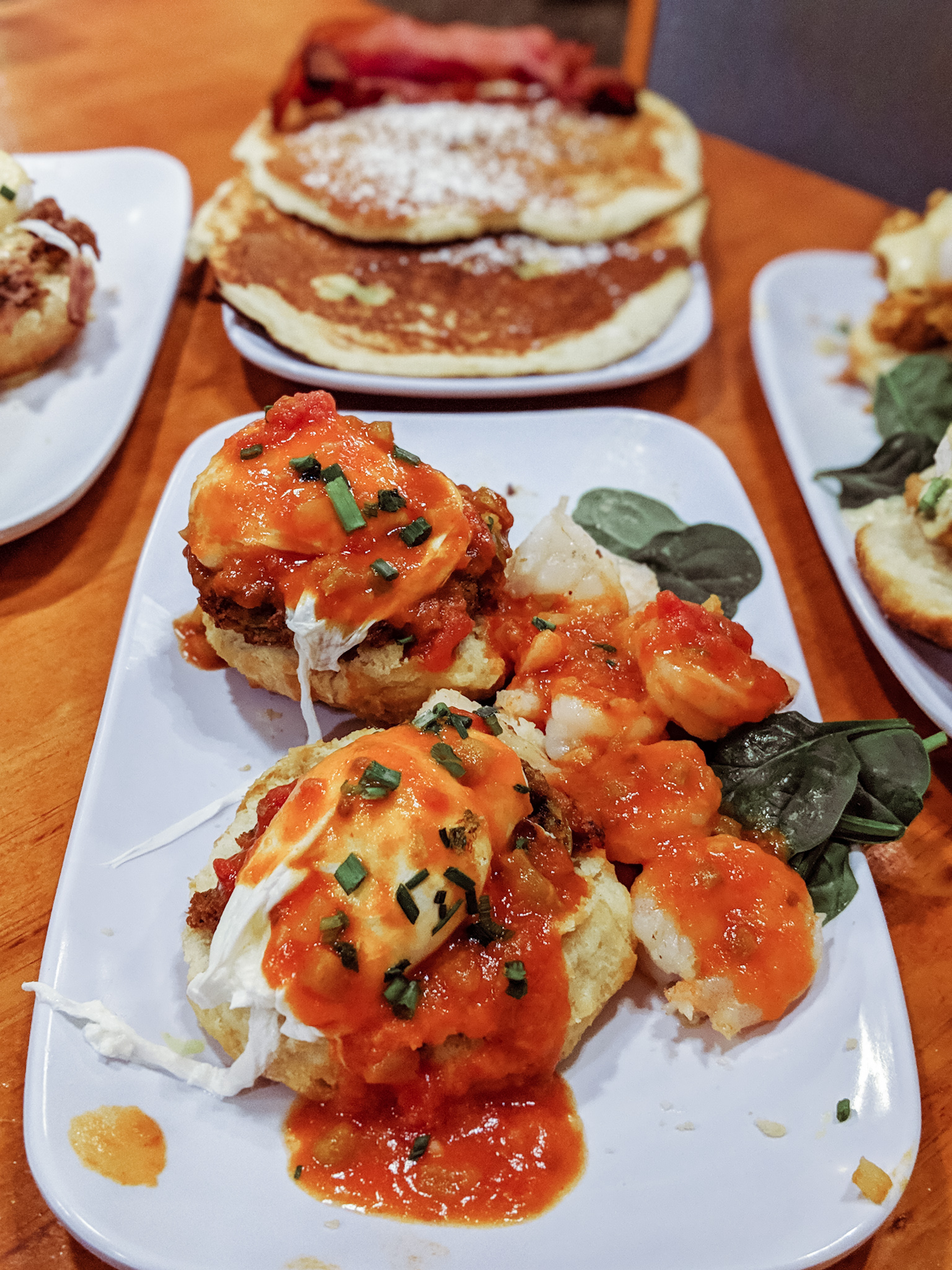 SHRIMP BOOGALOO BENEDICT: Gulf shrimp sauteed with pork tasso and creole tomato sauce served over fried green tomatoes, a buttermilk biscuit and two poached eggs