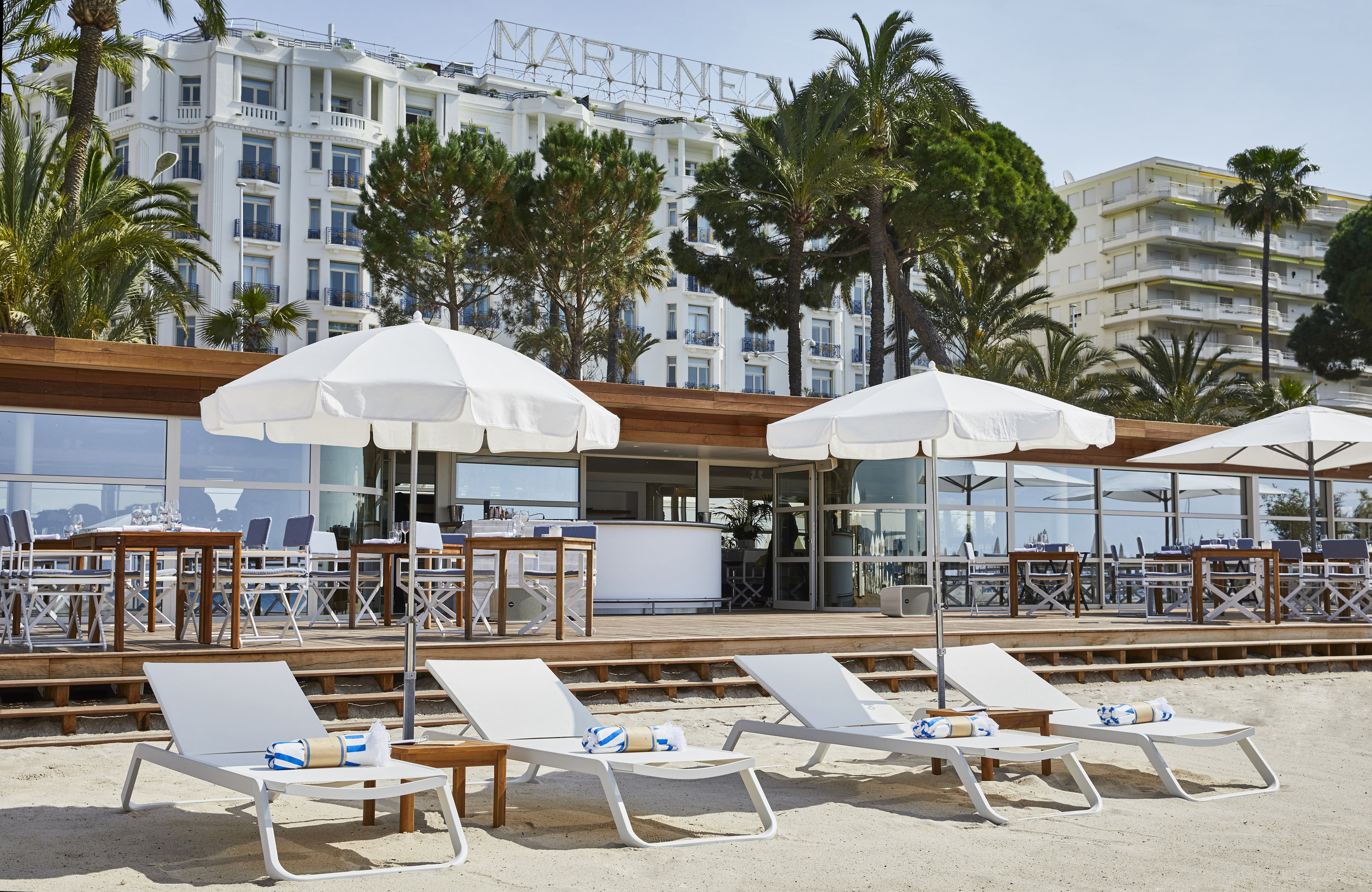 """La Plage du Martinez - Infinite blue waters and white sandy beach set the scene of your lunch with a view. """"La Plage du Martinez"""" private beach is the """"rendez-vous"""" spot for sunny days on the Croisette."""