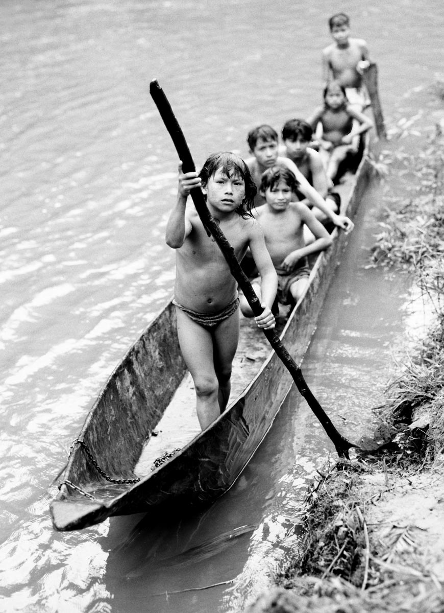 Kunang ( 8 ) using the dugout canoe to cross the river with his friends