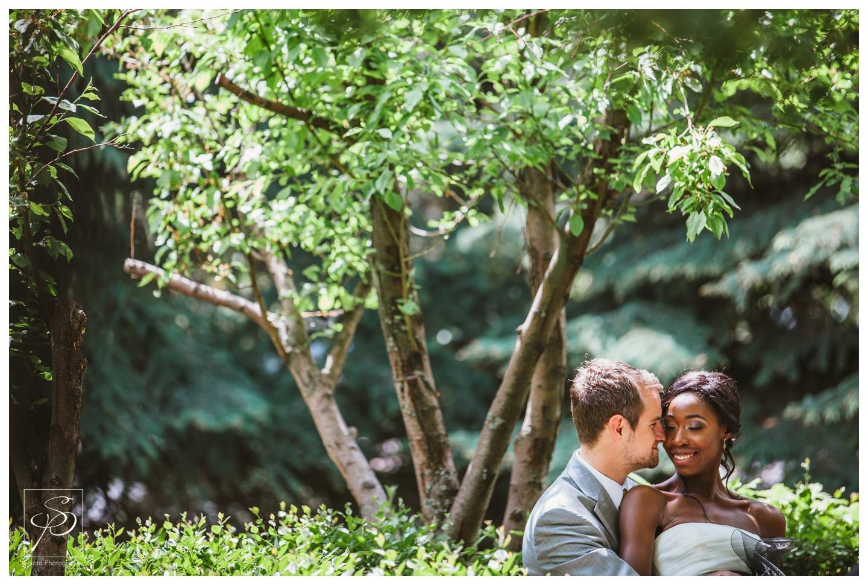 Bride and Groom posing under a tree in Woods Park Calgary