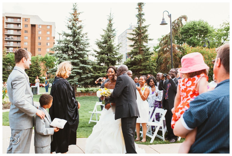 Father giving away bride at garden ceremony at Lougheed House Calgary
