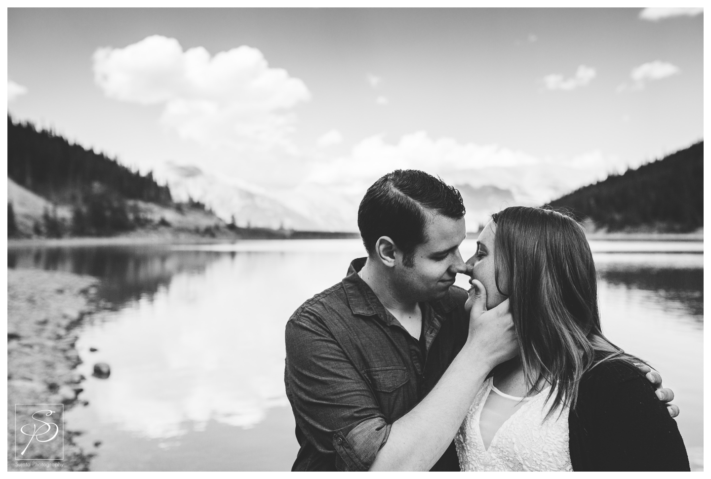 Couple kissing at the top of grassy lakes, Canmore