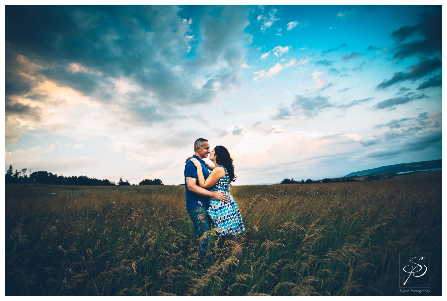 Couple embracing in a field in Ghost Lake, Alberta