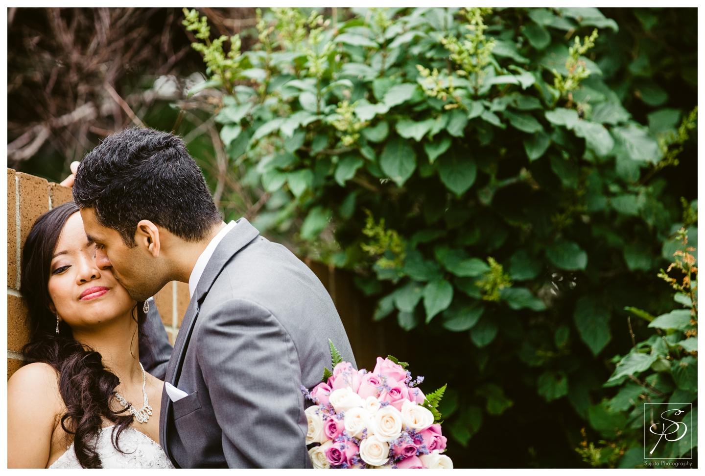 Groom kissing his bride on the cheek St. Thomas More Calgary