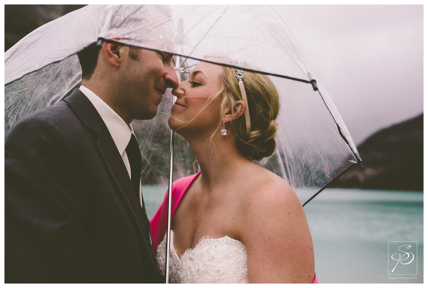 Bride and groom under umbrella in the rain at Lake Louise