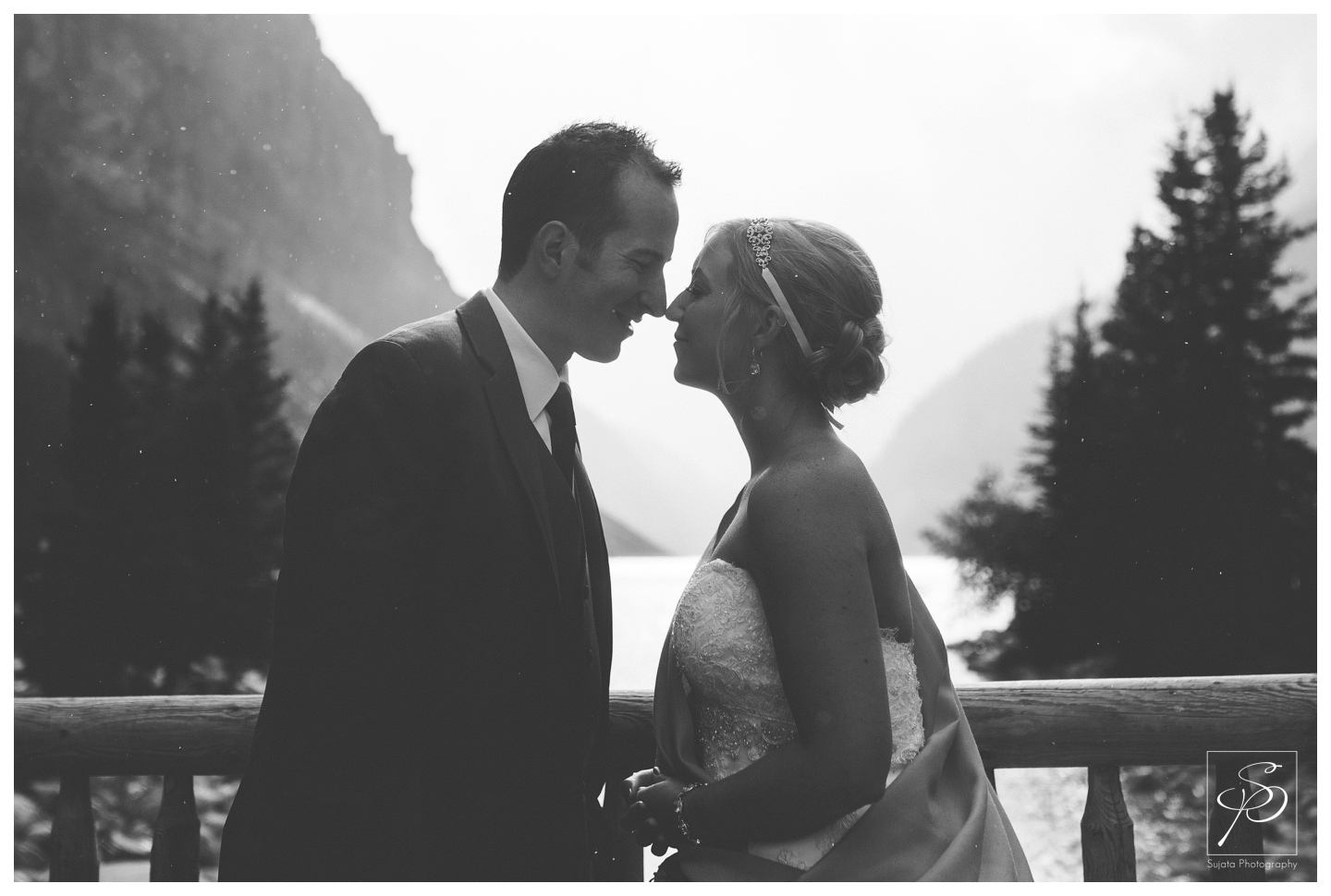 Bride and groom in summer snow storm at lake louise in Banff