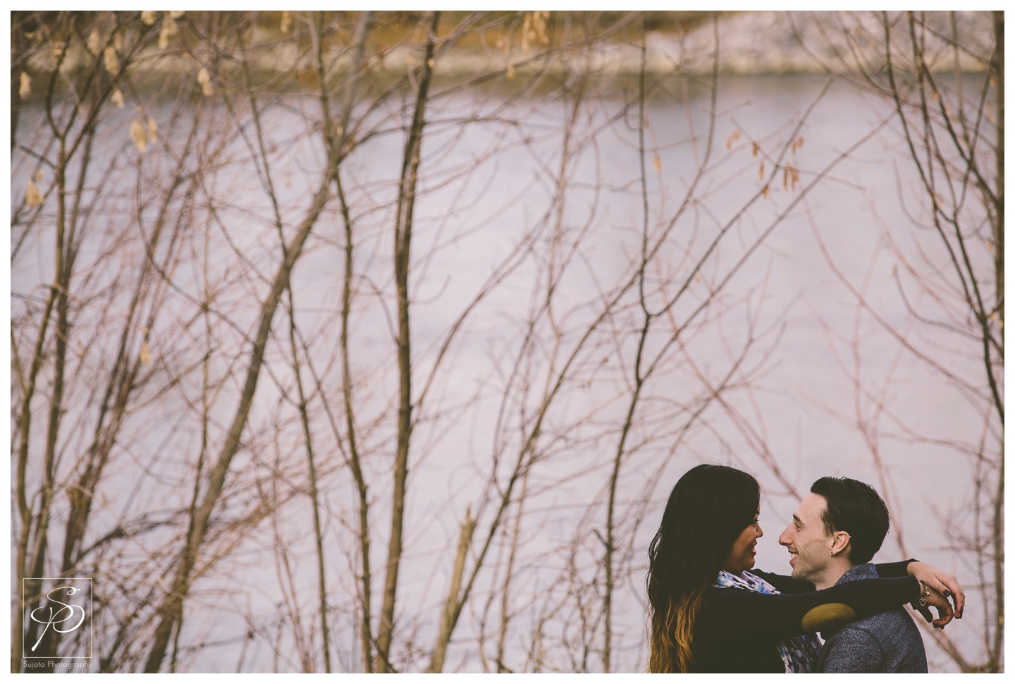 Couple cuddling by the river Calgary Engagement Photographer Crystal Sujata