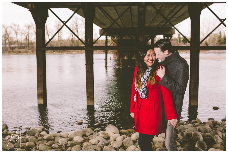 Couple posing under bridge Calgary Engagement Photography Crystal Sujata