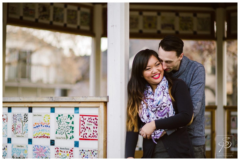 Couple cuddling under a gazebo Calgary Engagement Photographer Crystal Sujata