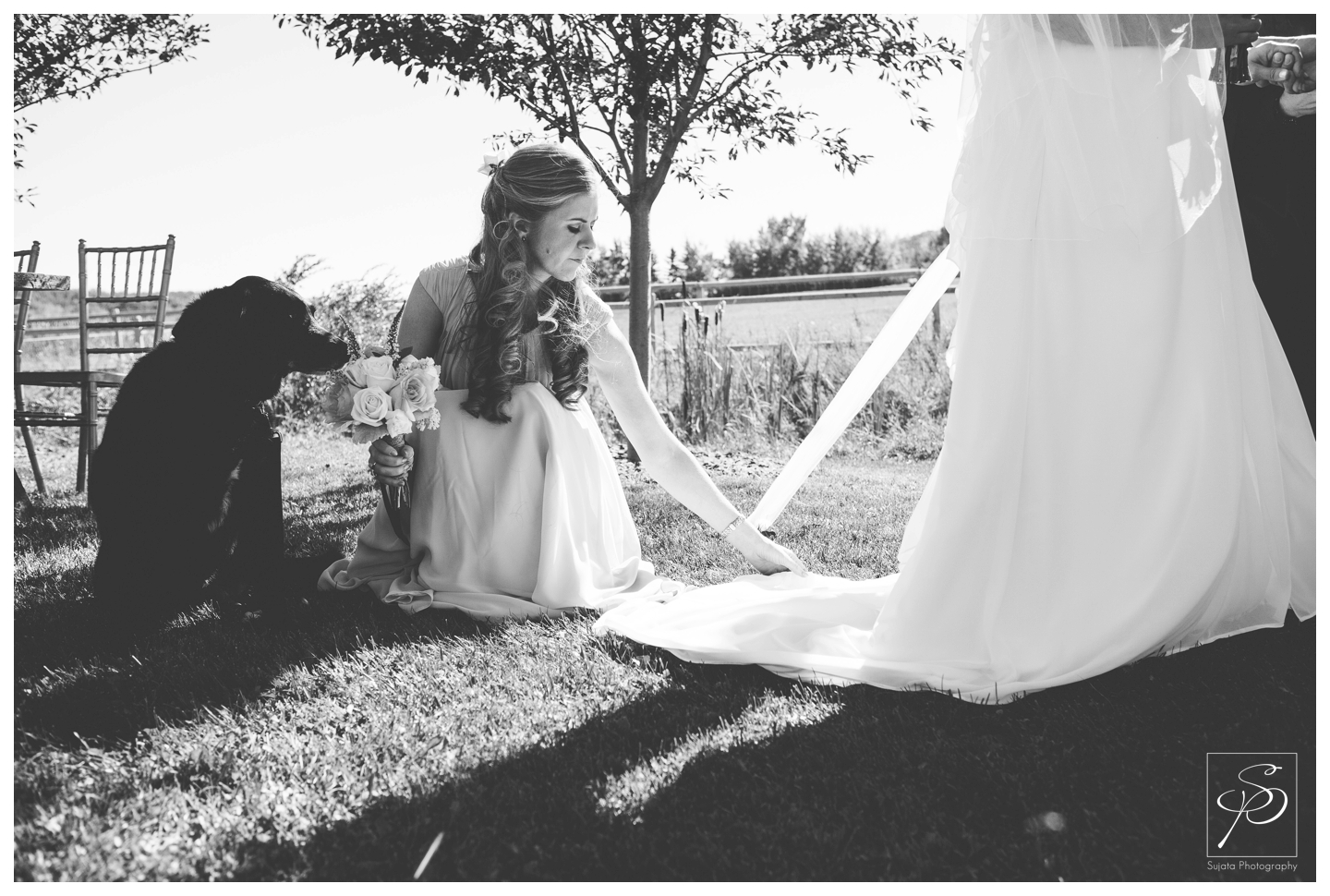 Bridesmaid fixing bride's dress outdoor wedding ceremony