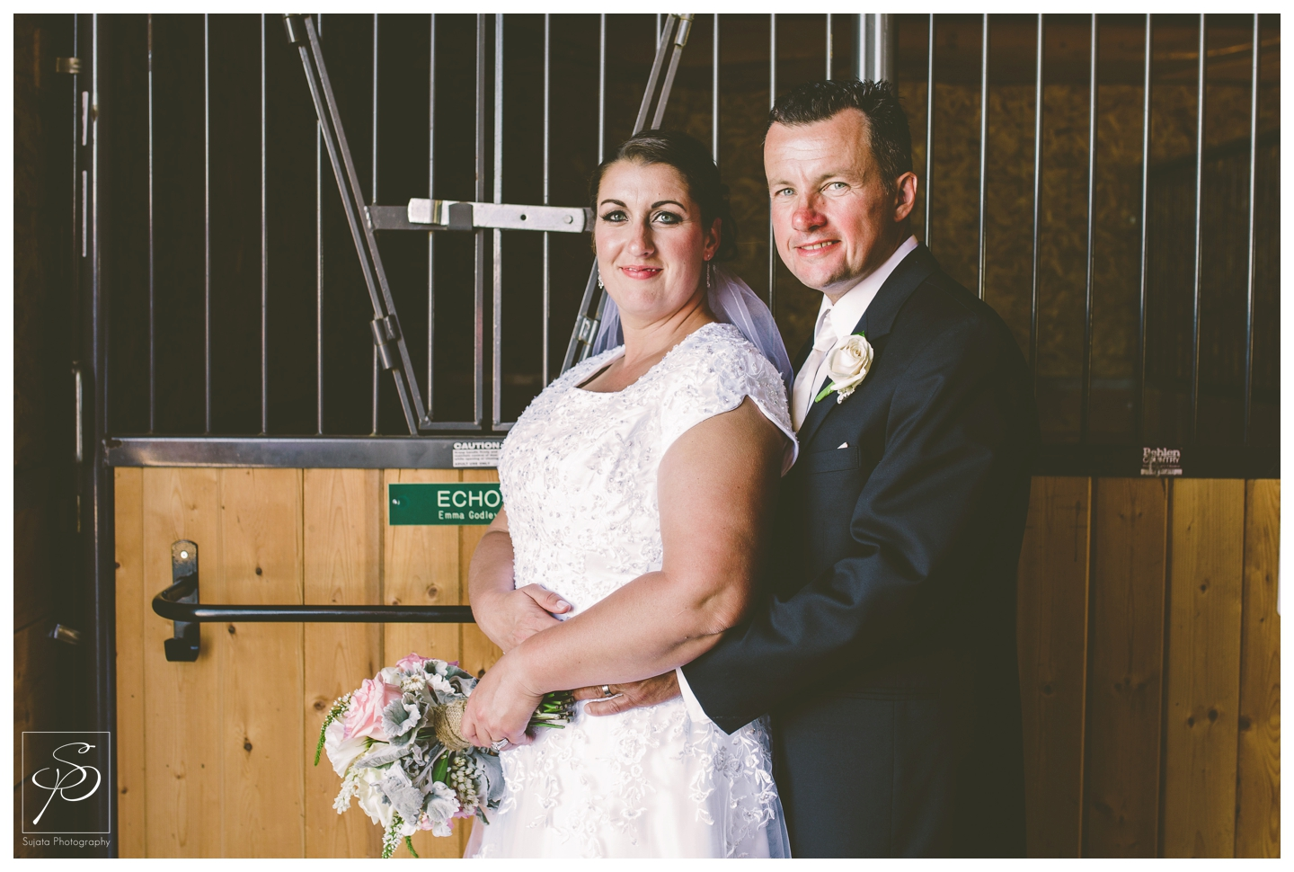 Bride and groom in barn at Okotoks acreage wedding