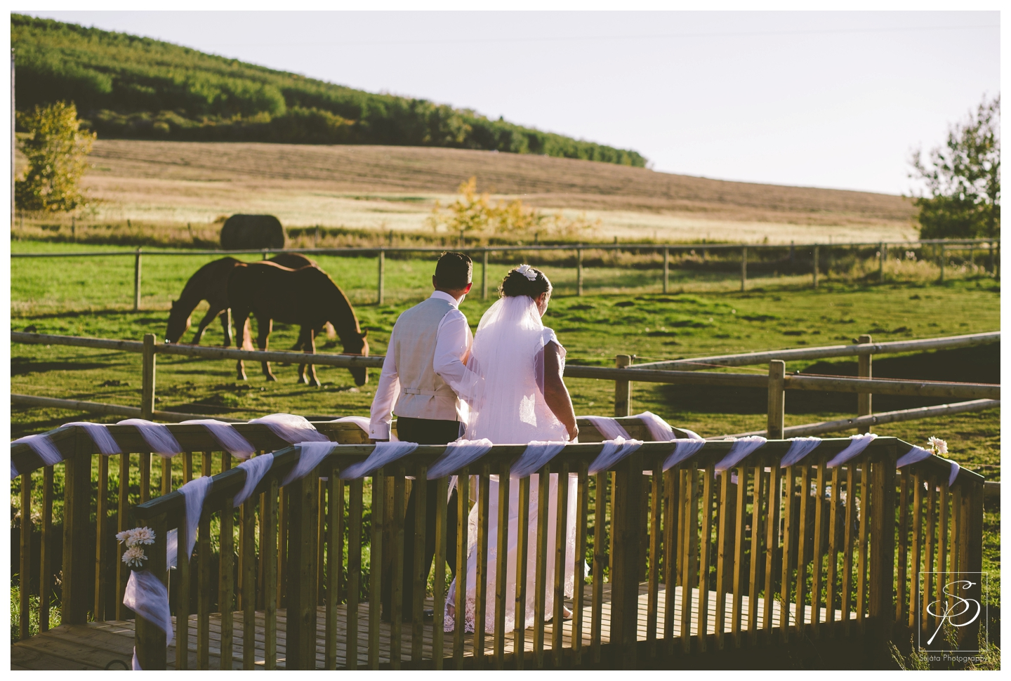 Bride and groom walking over bridge with horses