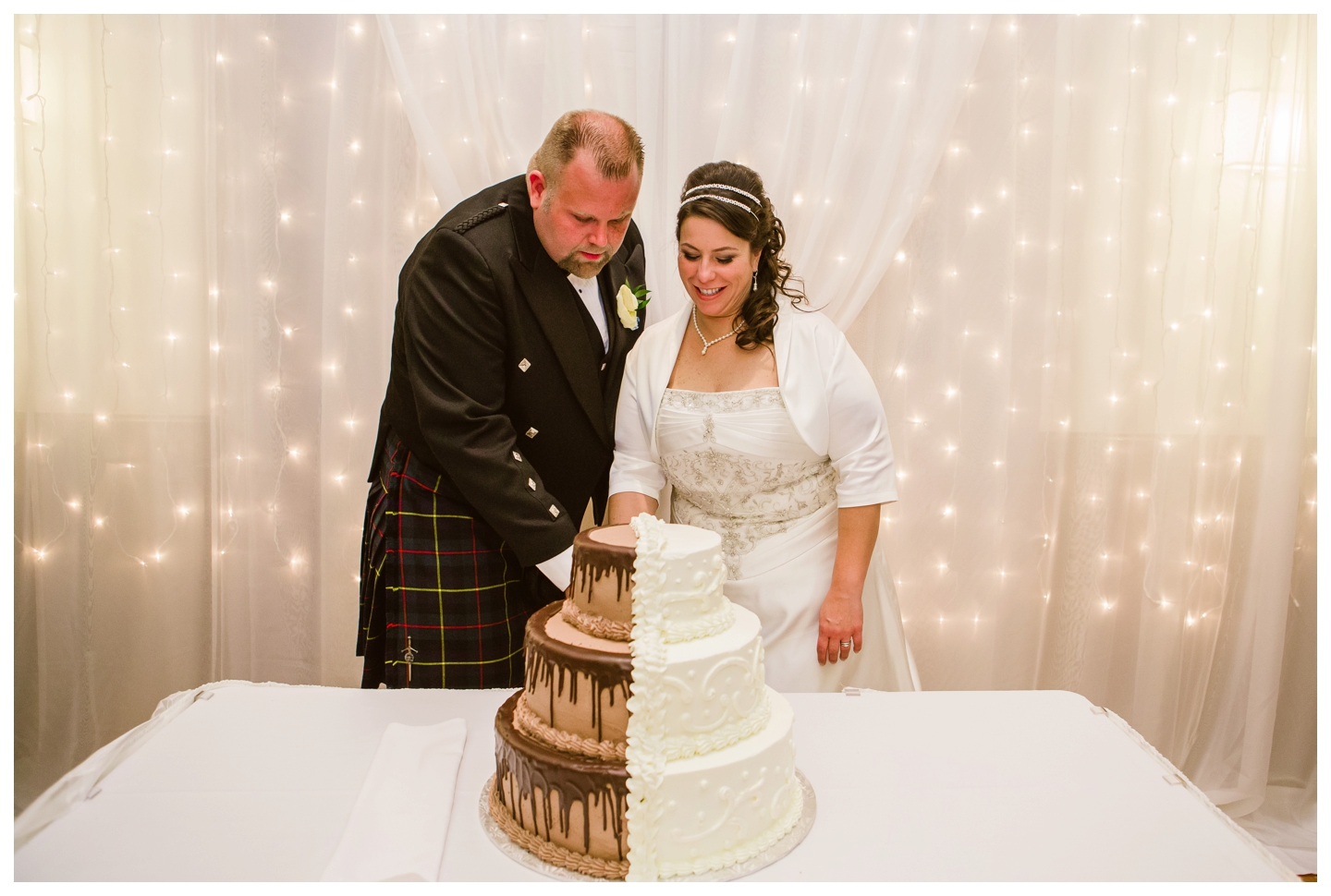 Bride and Groom cutting his and her wedding cake