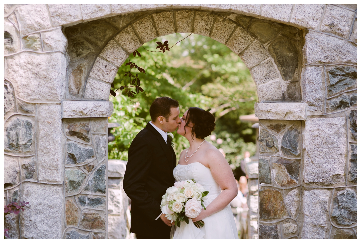 Bride and Groom kissing under stone arch