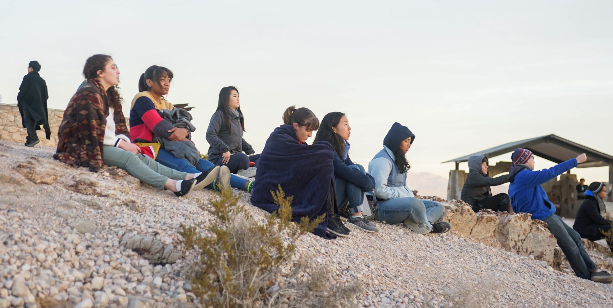 Retreat attendees meditating and watching the sun rise at Exploration Peak