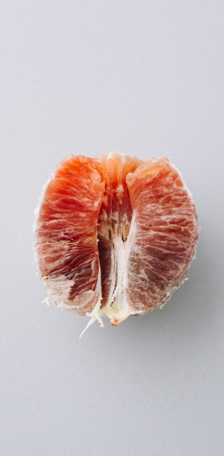"""ii. pineapple - I grate my tongue on my teeth to remove the imaginary fuzz. Allergic? Possibly. I once read in 10 Ways to Make your Vagina Taste Delicious that this is what people wanted. By people I mean men—but I don't sleep with men anymore.""""Do you miss it?"""" my girlfriend asks.The acidic striping of my taste buds tells me I don't. It always felt like a show—a charade of sorts. A dimly lit world where mattresses became bowls and they hardened as I forced myself to mold into them.I didn't hate men, they did however, represent the unknown parts of myself. The masculinity that also feels like a phantom that lives in my sheets—but I have always been a masochist for love.I consume pineapples for snacks now, reminiscing on a time when I ate citrus for pheromones. My relationship to nature feels like walking barefoot on stones—I prop myself on tip toes to avoid the sharp pain in the soft middle of my sole.My girlfriend and I now use this fruit as a safety word. We scream """"Pineapple!"""" when the other has gone too far.I will say my boundaries have become blurred. I use this word when I feel like breaking. Setting fire to anything. Offering imaginary casualties. Left to define clarity. Bastardizing myself.Berating.The sun shines through and casts a form on the counter that reminds me of a shadow world, one I don't go to anymore. I think of California. I taste street lights and the particles that circle dance in its cone. I buy a Big Stick from the ice cream truck and search for the flavor hidden in fructose. I'm dissatisfied by shape and girth. So, I turn to coconut pops and bite the sides until it hurts."""