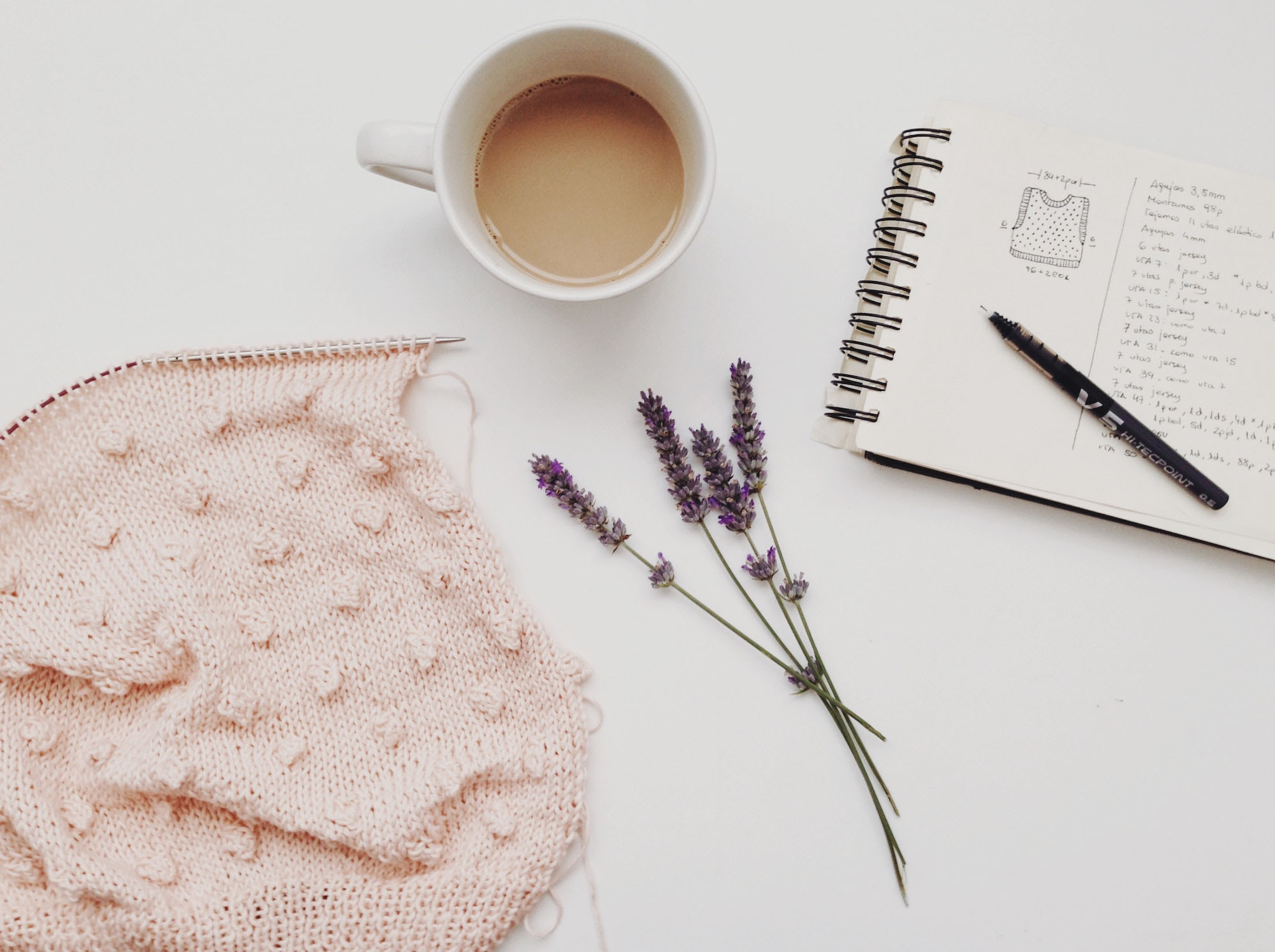 knitting a baby grow and notebook on white table.jpg
