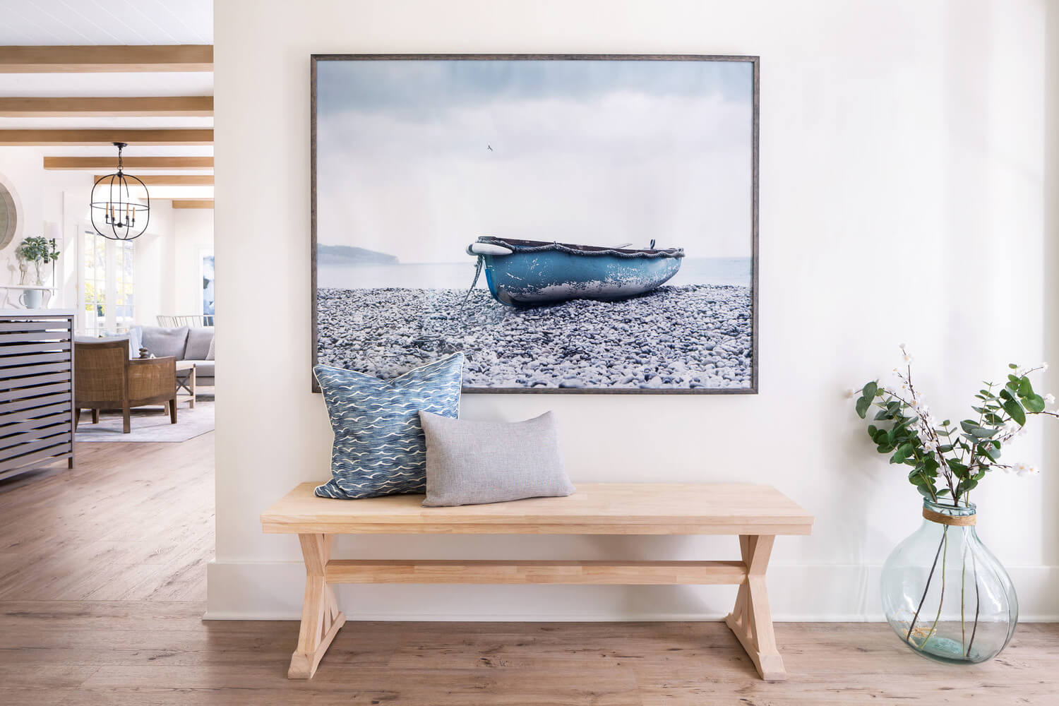 entryway with picture of boat and a plant in a large vase
