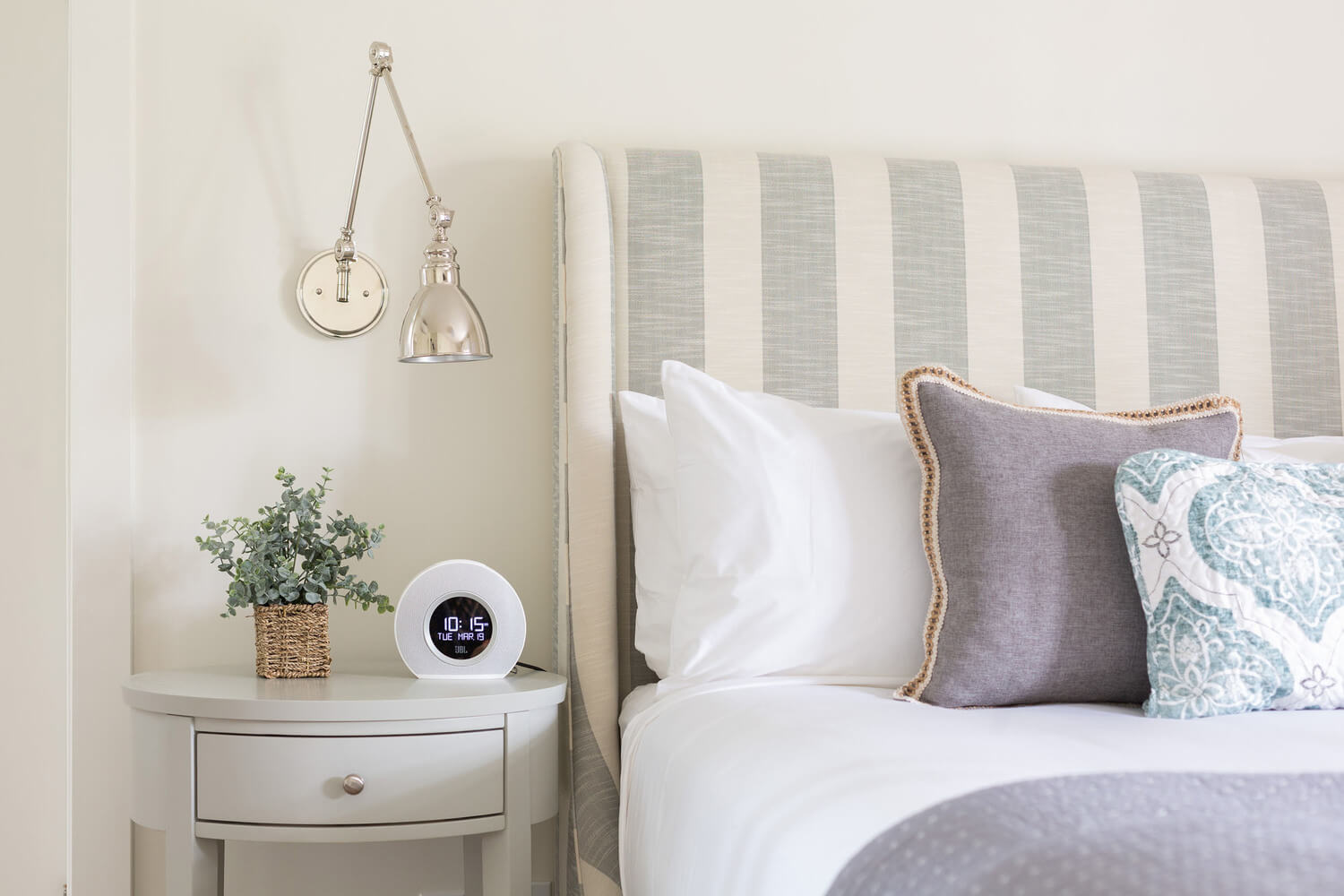close up of bedside table with a plant, clock and lamp