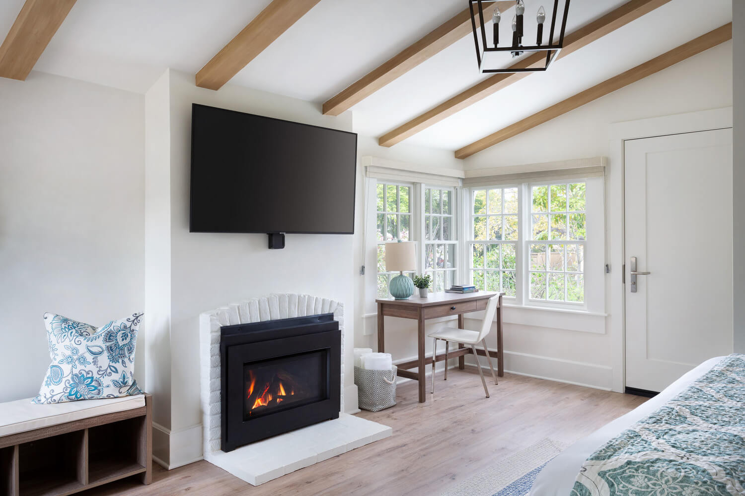suite with desk, tv and fireplace and decorative floral pillow