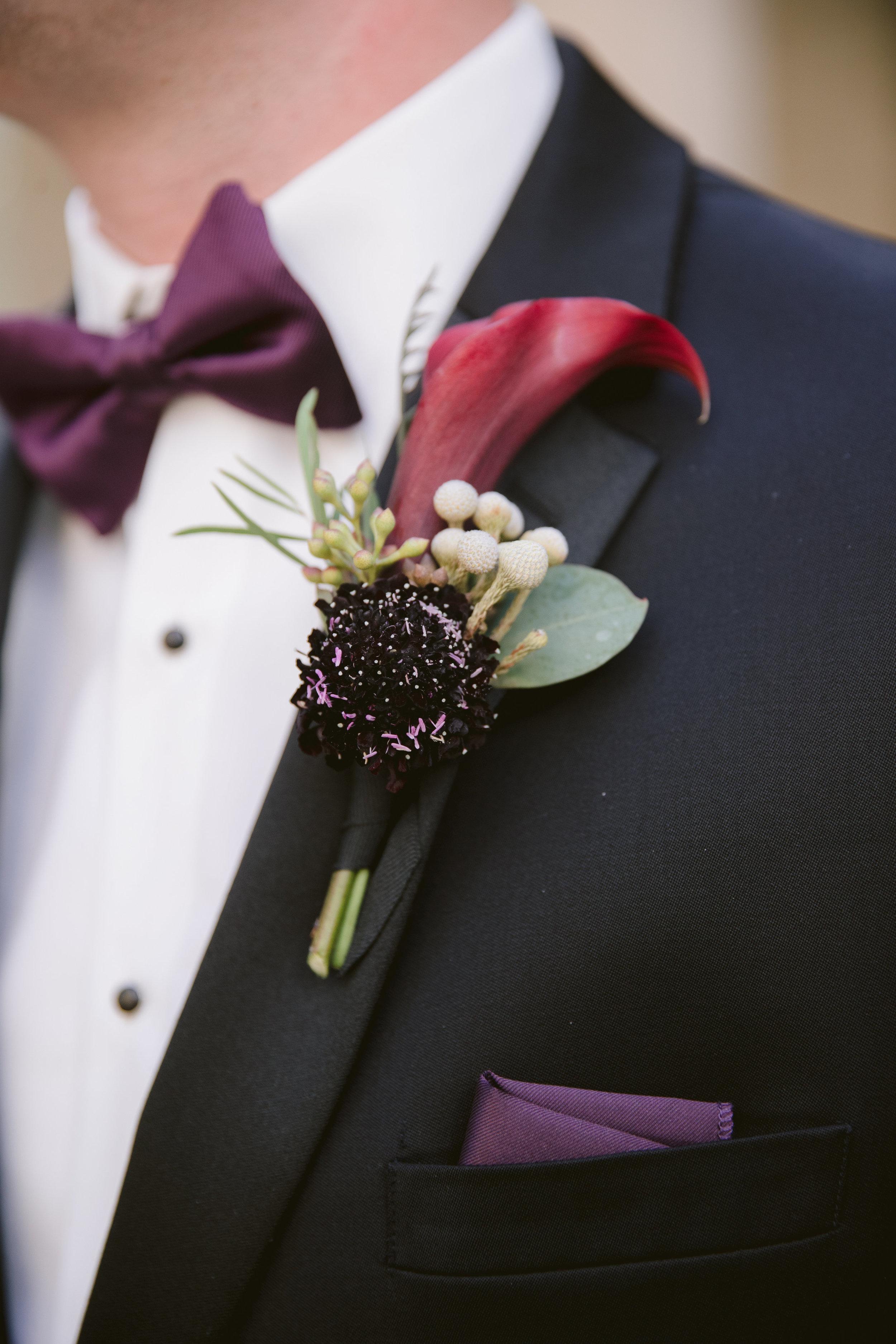 Purple wedding boutonniere. Photo by Laura Stone Photography.
