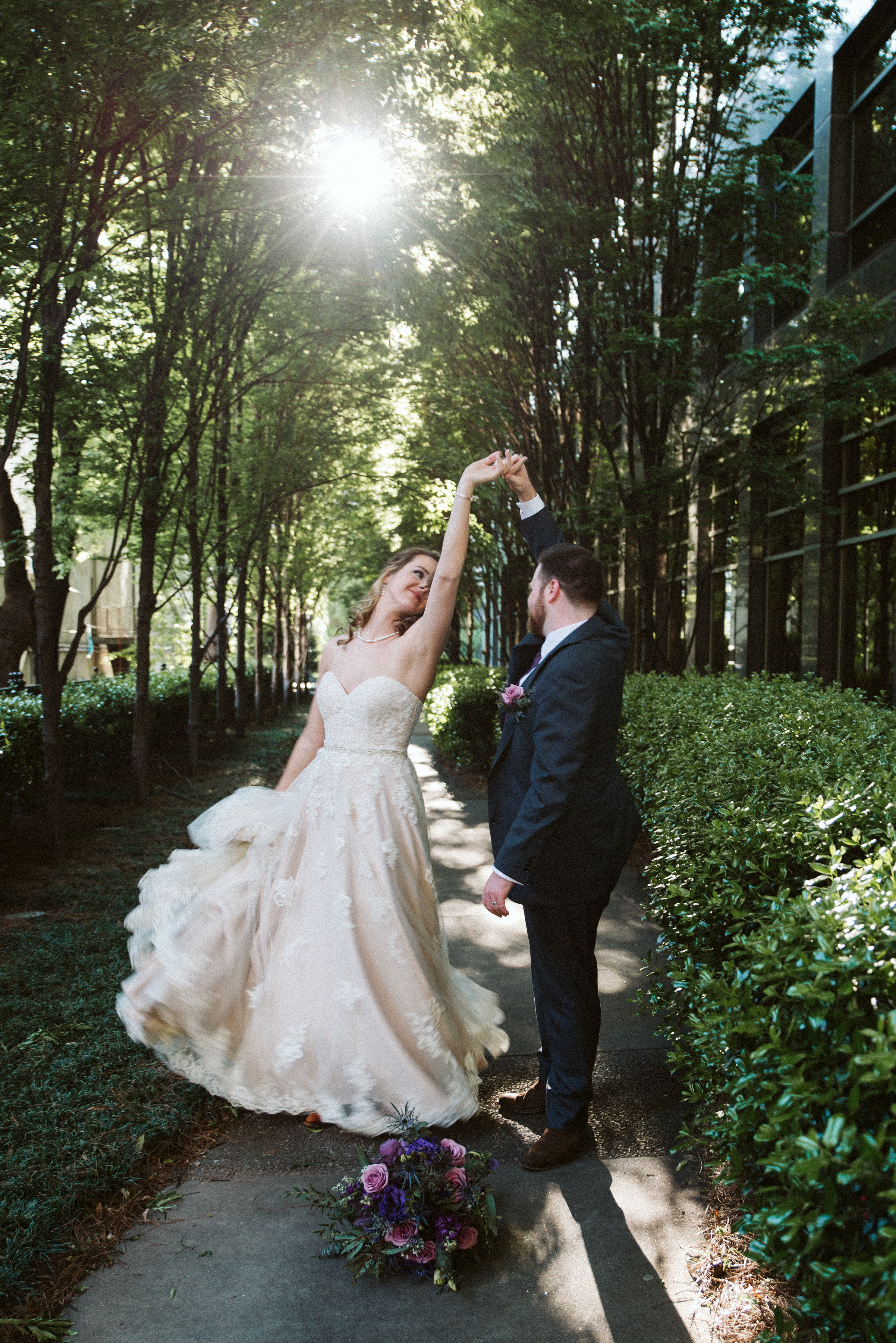 Groom twirls his bride beneath a sunlit canopy.