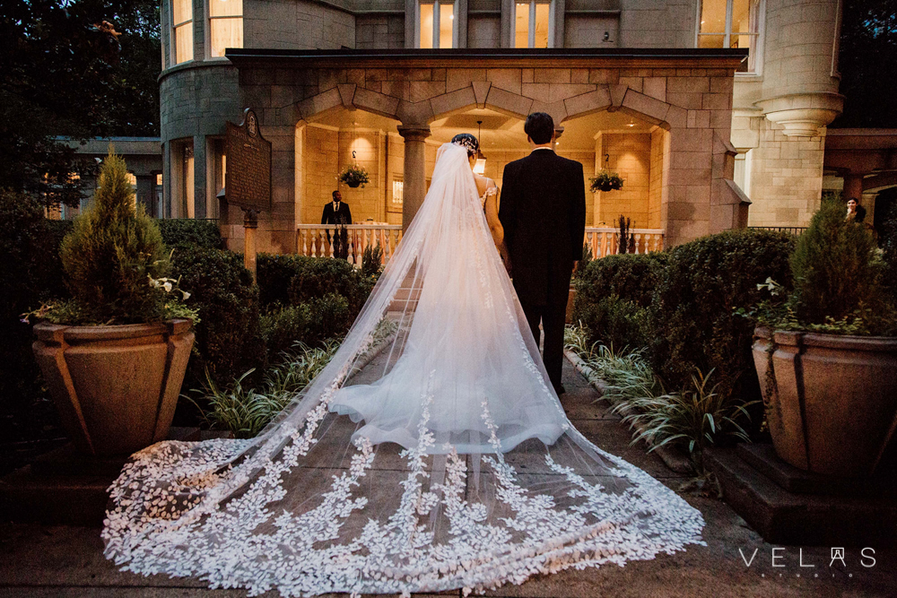 Bride with cathedral veil and groom in front of The Wimbish House.