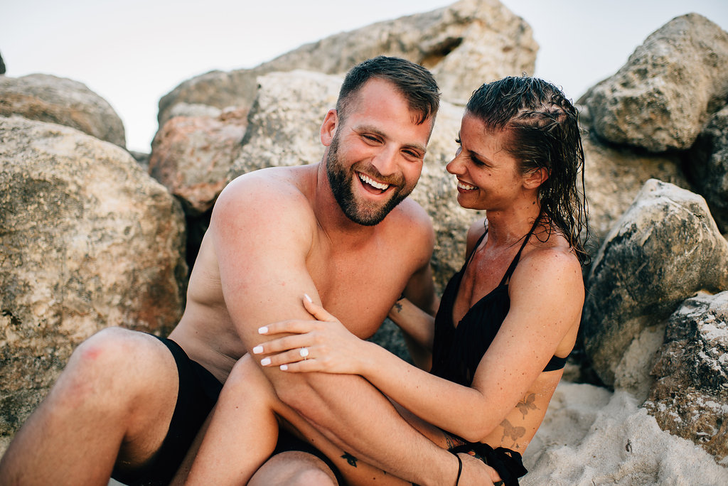 engaged couple laughing while sitting in the sand at Royalton White Sands in Jamaica
