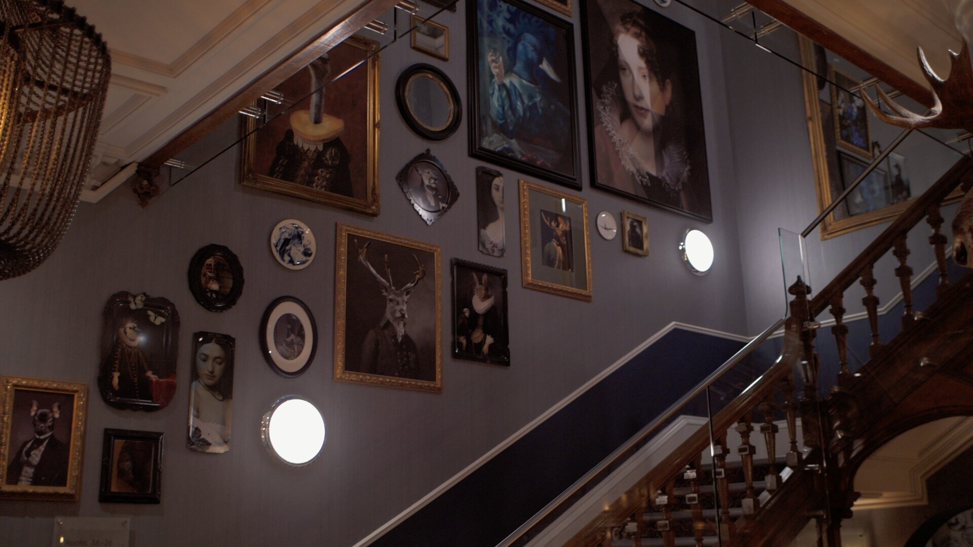The staircase in the 'Oddfellows on the Park' hotel that features many pieces of artwork. All the art is very quirky with images of animals wearing human clothing and accessories.