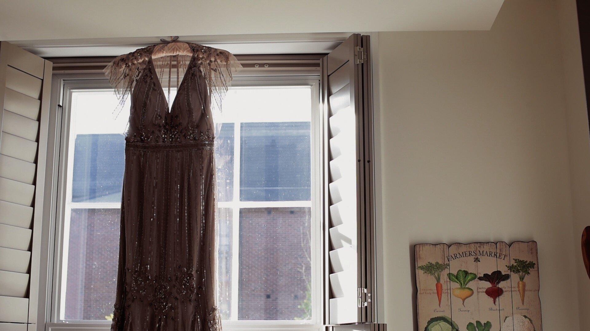 The brides dress hung in front of a window. The dress is salmon pink in colour and heavily inspired by the burlesque era.