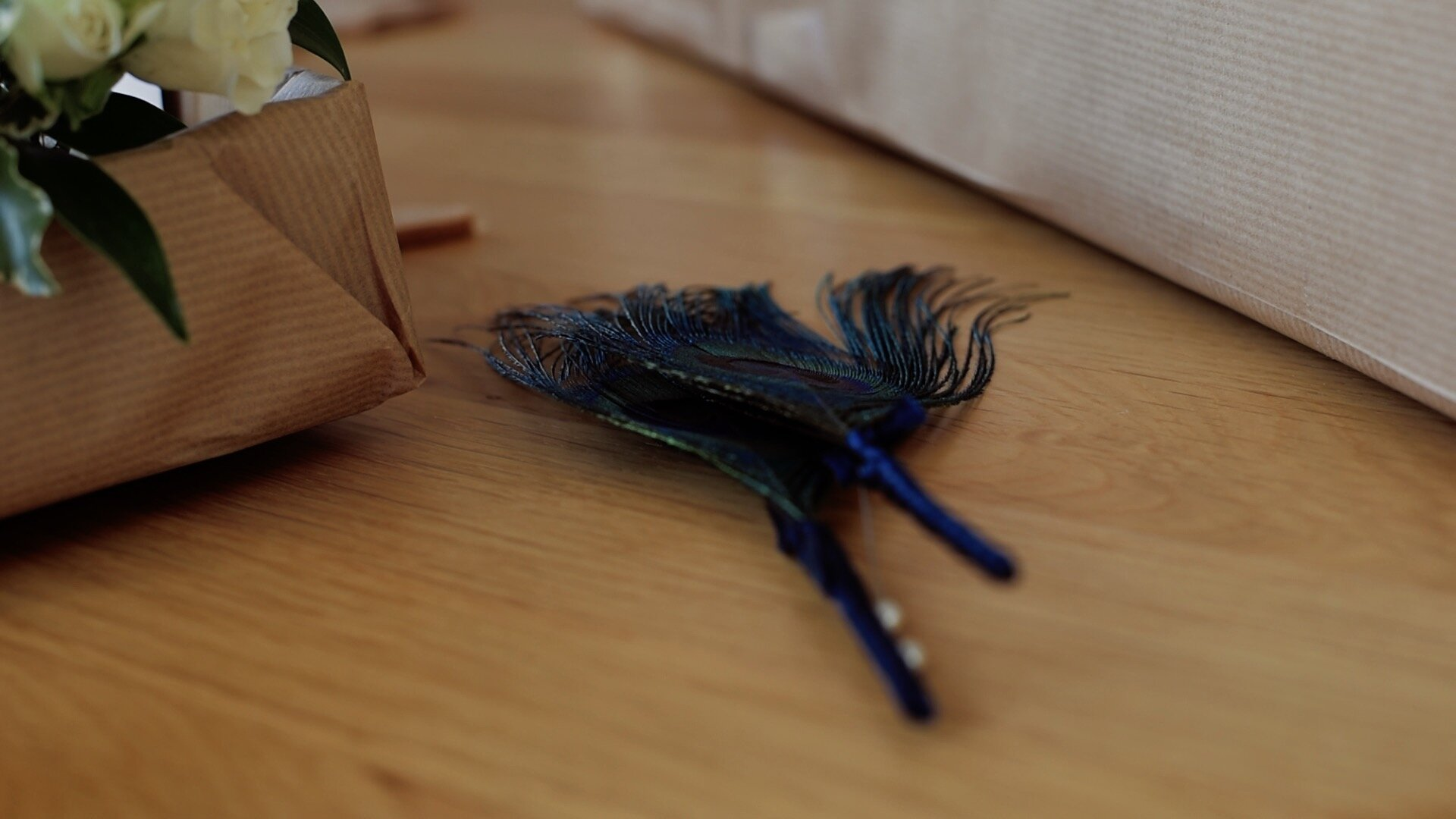 An image of the peacock feather buttonholes that were produced for the groomsmen by 'Blue Door Flowers'