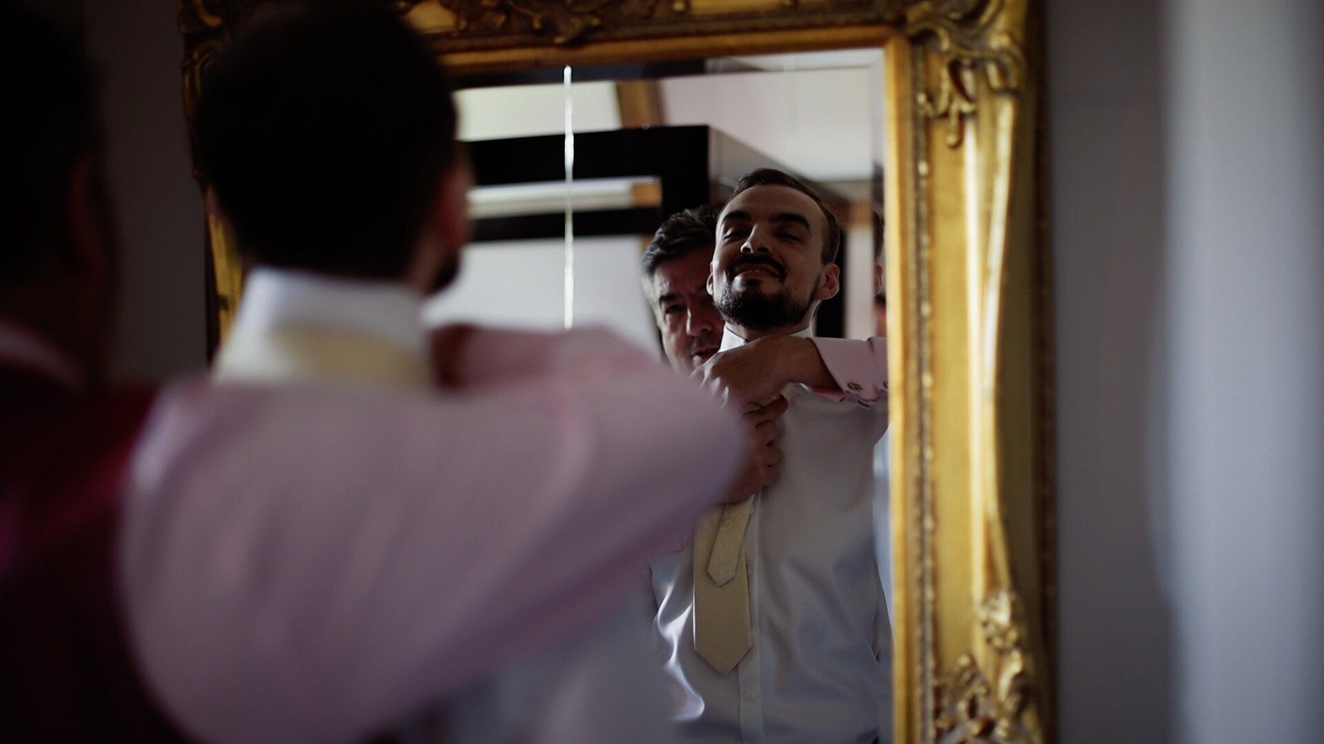 The groom getting his gold tie made into a Windsor knot with the help of his father.