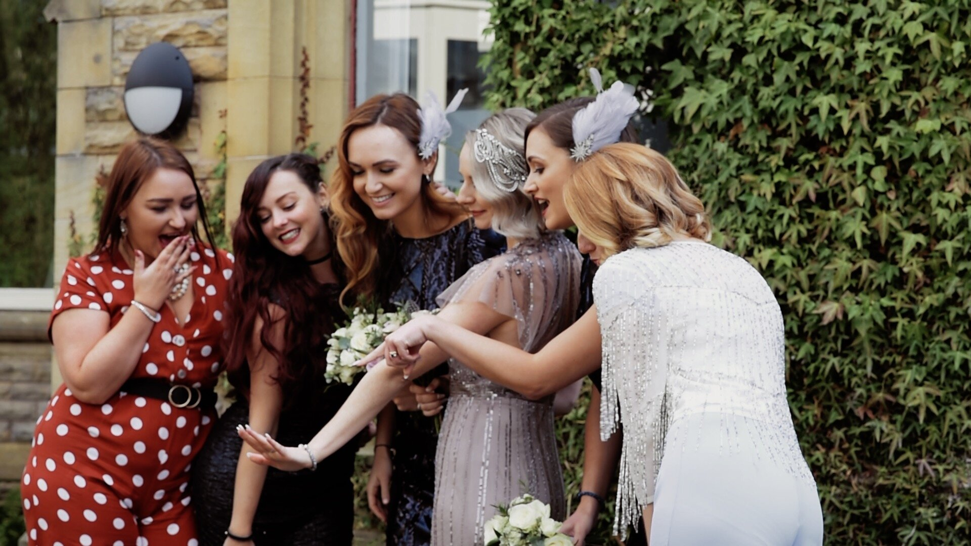 The bride having a picture taken with her bridesmaids and friends. They are all looking at her wedding ring and pointing in shock to the fact that she is now officially married.