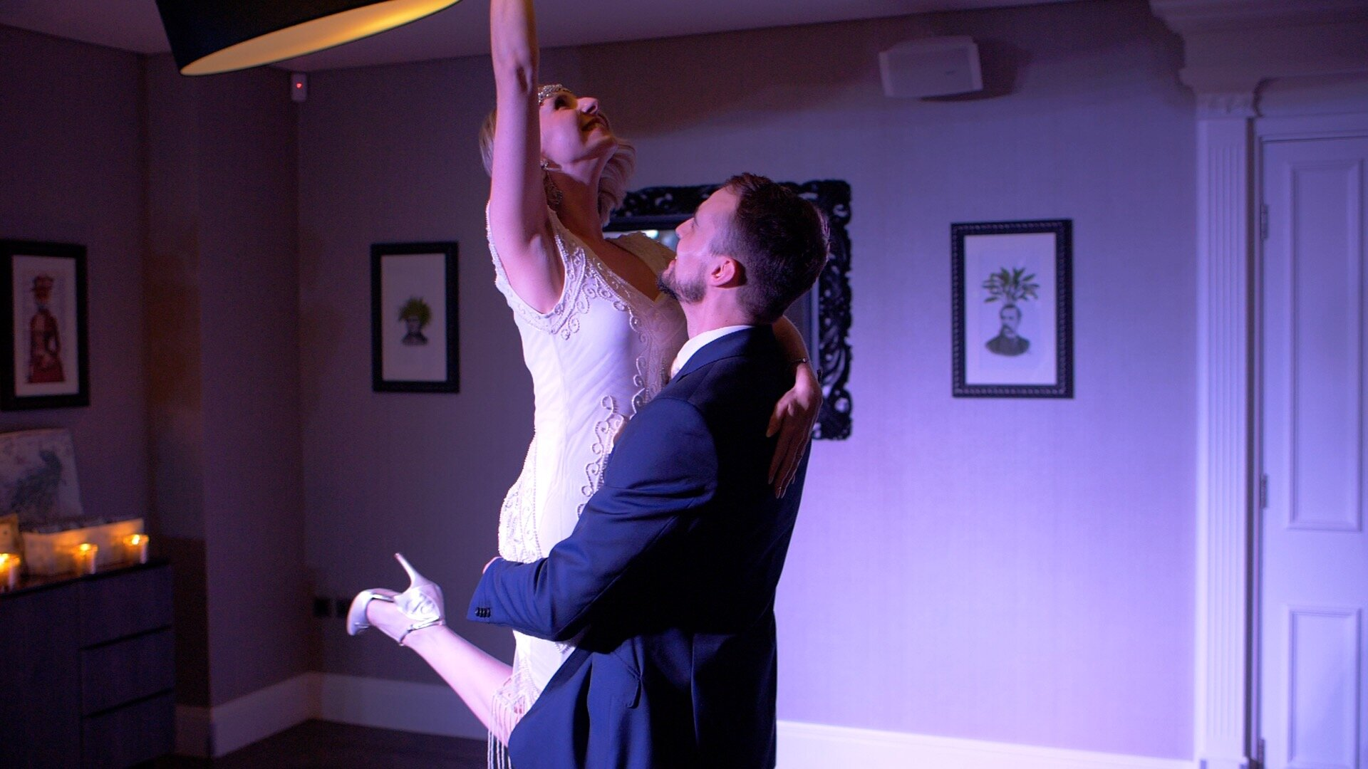 The bride and groom in the middle of their first dance. The groom is holding the bride up by her legs. The bride is gracefully lifting one of her arms in the air.