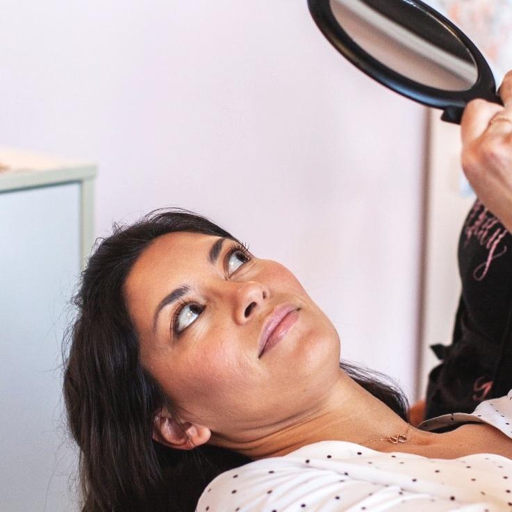 Brow Betty Customer looking in mirror after eyebrow waxing