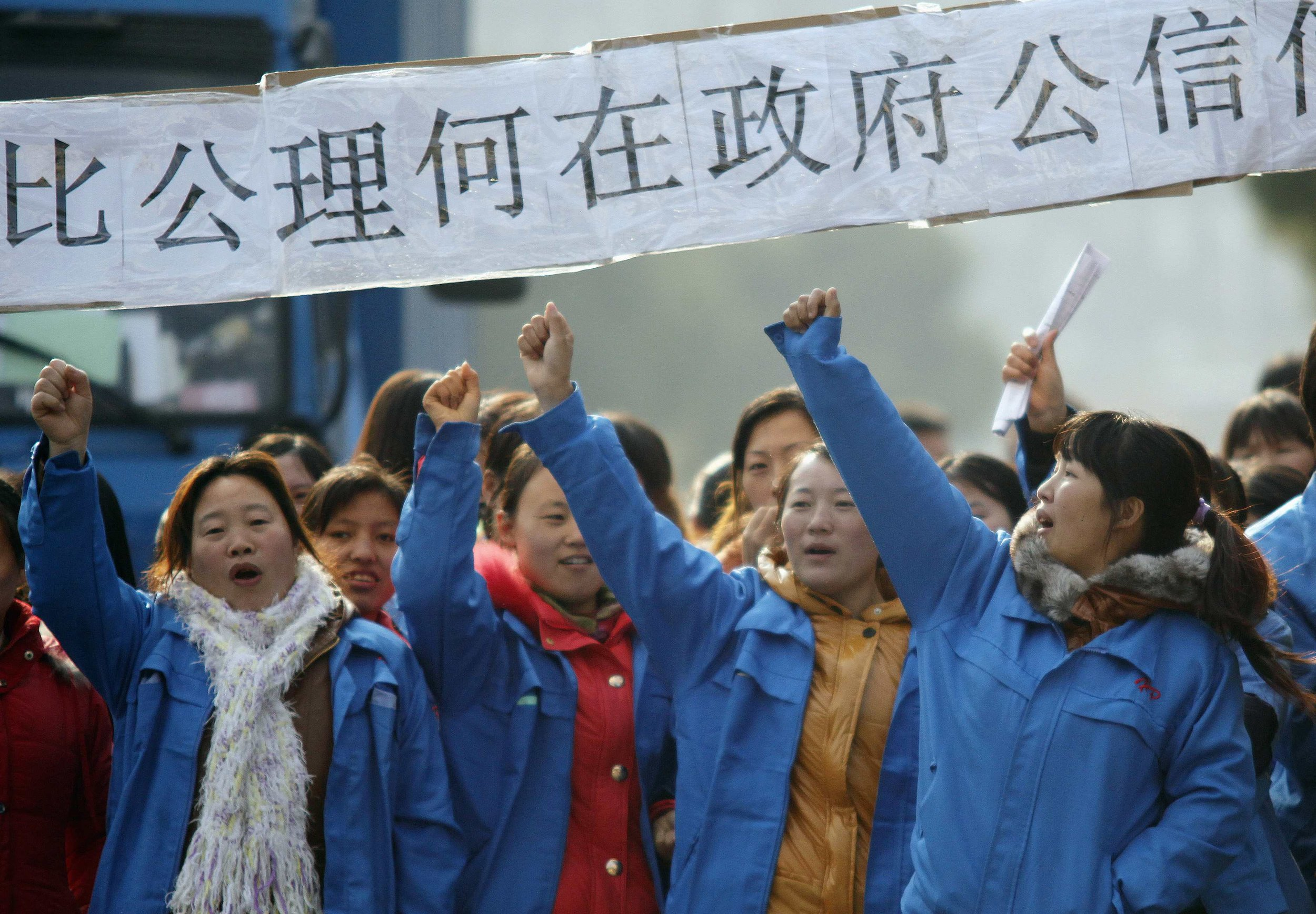Workers on strike blocking the entrance gate of Hi-P International factory yell slogans during a protest in Shanghai in December 2011. (Reuters/Carlos Barria)