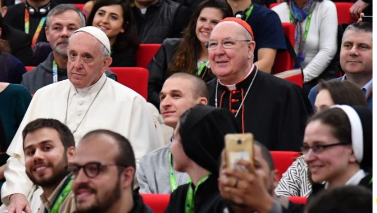 Pope Francis and Cardinal Farrell sit with students at the 2018 pre-synodal meeting for young people.