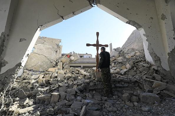 Member of the Syrian Arab-Kurdish forces places a cross in the rubble ahead of a  Christmas celebration at the heavily damaged Armenian Catholic Church.