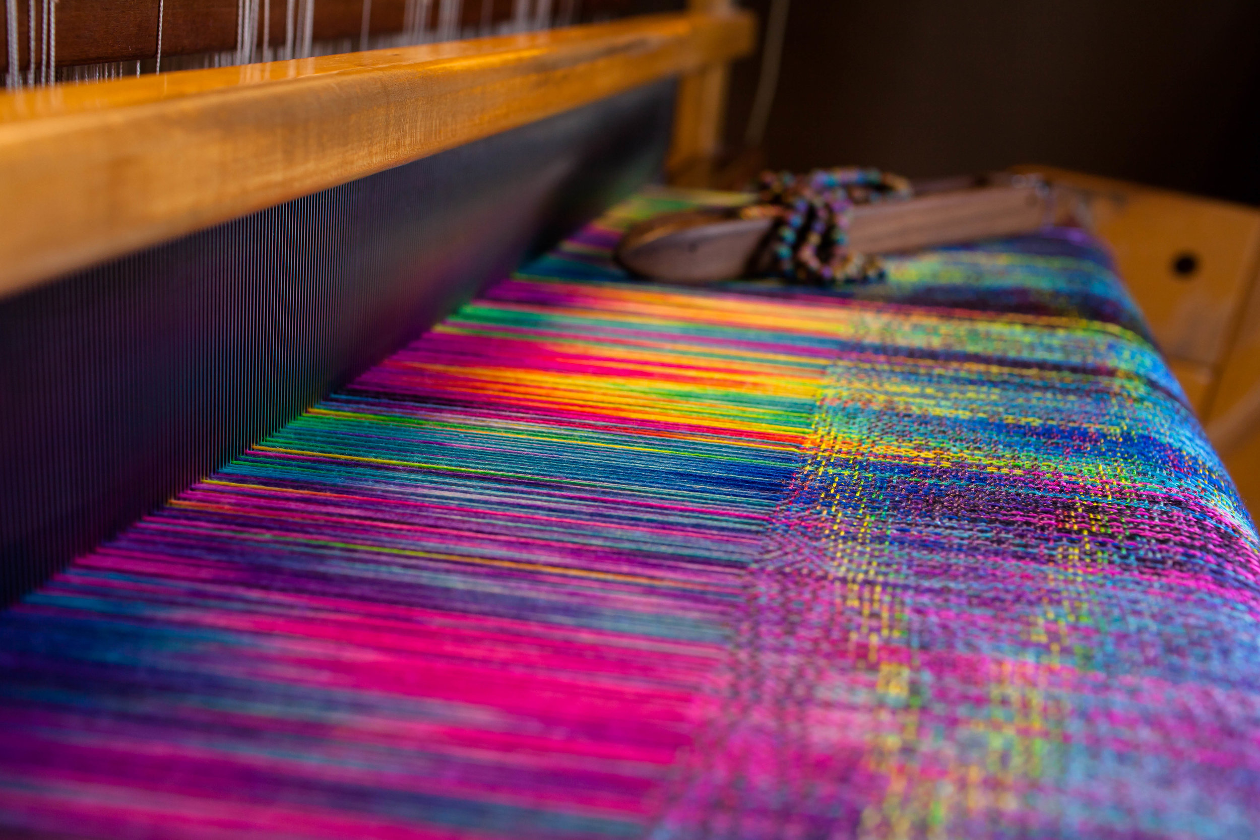 VALHALLA  Photo ID: photo shows a rainbow fabric though the loom reed, a shuttle is placed in the background decorated with beads
