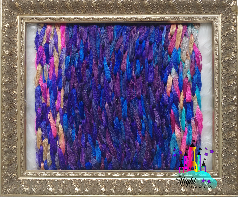 CAIR PARAVEL  photo ID: a gold picture frame is surrounding painted yarn in a fluffy white background. It's chained with bold blues and purples with Huntsville of pink and cream. The alight handwovens watermark is in the bottom right corner