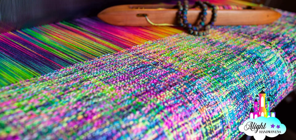 Photo ID: Photo of a loom with a rainbow woven wrap, on the wrap is a shuttle with decorative beads and the Alight Handwovens Watermark in the corner.