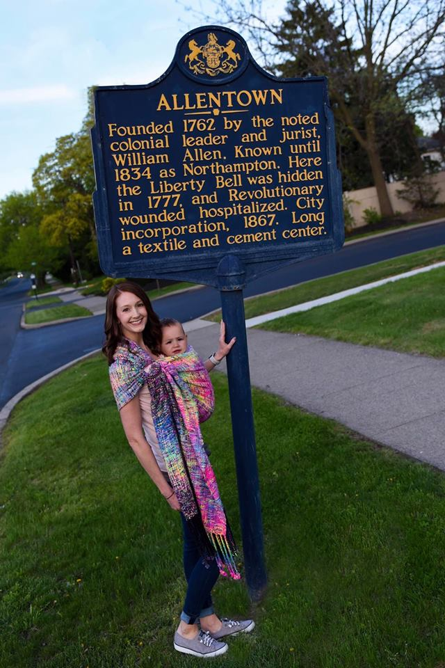 Photo ID: a brunette white woman is wearing her white baby in this dark rainbow ring sling. They are outside in the grass standing next to the town sign of Allentown, PA