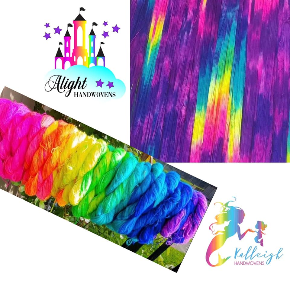 photo ID: a photo showing a warp laid out and rolled up in purples blues with hints of yellow and green and pink. The top left is the alight castle watermark and the bottom right corner sows the kalleigh handwovens watermark