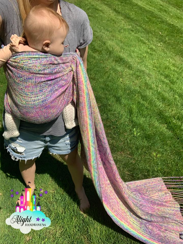 Traditional Sling Carry (torso variation)  photo ID: a momma wearing her baby girl in a torso carry with a beautiful pastel rainbow ring sling. They are outside in the grass. The photo shows the alight Handwovens watermark