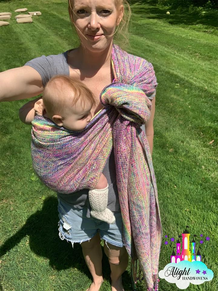 Traditional Sling Carry  photo ID: an angled view of a red haired momma wearing her baby girl on her front in a rainbow ring sling. They are standing in the grass and the Alight Handwovens watermark is in the bottom right corner.