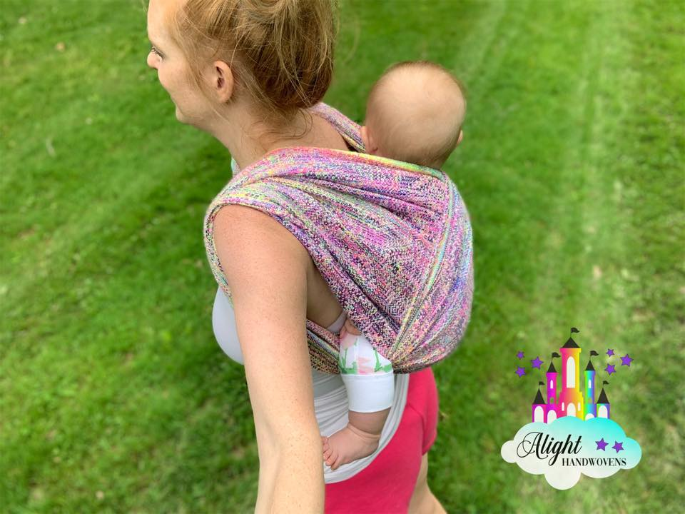 Short Back Cross Carry  photo ID: a side view of a red haired momma wearing her baby girl on her back in a pastel rainbow wrap. They are outside in the grass and the alight Handwovens watermark is in the right corner.
